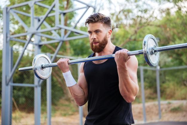 Ritratto di un muscoloso giovane uomo barbuto che si allena con bilanciere all'aperto