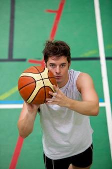 Ritratto di un giovane muscolare che gioca a basket-ball