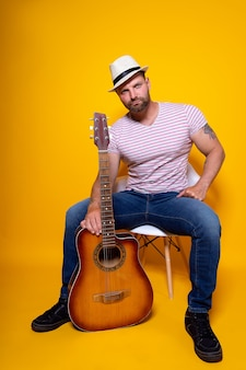 Ritratto del musicista che suona la chitarra acustica e canta una canzone emotiva. bardo famoso