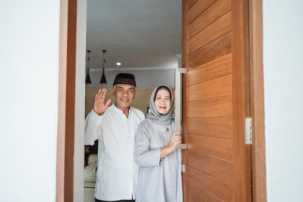 Ritratto delle coppie senior asiatiche musulmane che stanno davanti alla porta d'ingresso in attesa della famiglia a venire