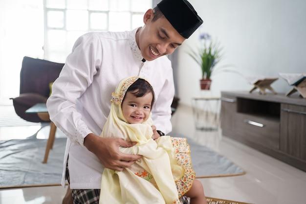 Ritratto del padre musulmano che insegna alla sua figlia sveglia come pregare a casa