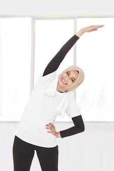 Ritratto di donna sportiva musulmana che fa allungamento della mano e del corpo