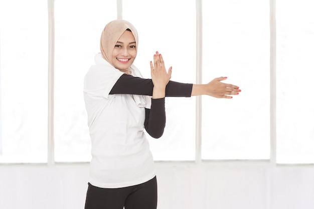 Ritratto di donna sportiva musulmana che fa allungamento della mano mentre sorride