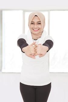 Ritratto di donna sportiva musulmana che fa allungamento della mano
