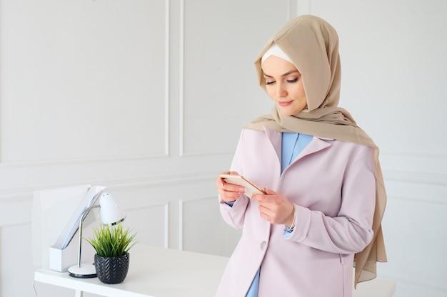 Il ritratto della donna musulmana in hijab beige sta leggendo qualcosa sul telefono cellulare