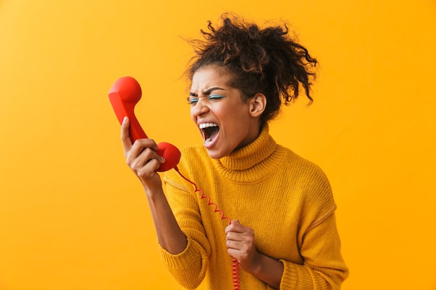 Ritratto di donna afroamericana nervosa con acconciatura afro che urla mentre parla sul ricevitore rosso, isolato
