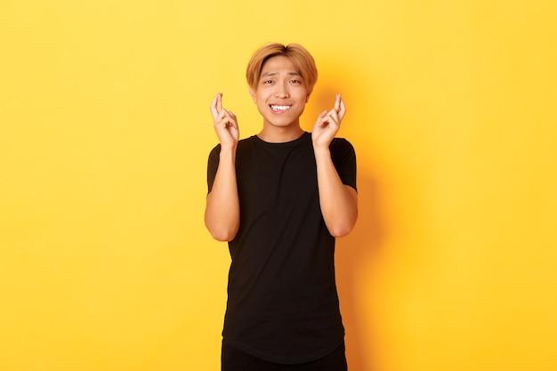 Ritratto di ragazzo asiatico nervoso incrocia le dita buona fortuna, esprimendo un desiderio, pregando sul muro giallo