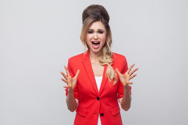 Ritratto di bella donna d'affari nervosa con acconciatura e trucco in blazer rosso fantasia, in piedi, guardando la macchina fotografica e urlando. girato in studio al coperto, isolato su sfondo grigio.