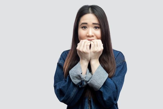 Ritratto di bella giovane donna asiatica castana scioccata nervosa in giacca di jeans blu casual con trucco in piedi che si morde l'unghia e che guarda l'obbiettivo. girato in studio, isolato su sfondo grigio chiaro