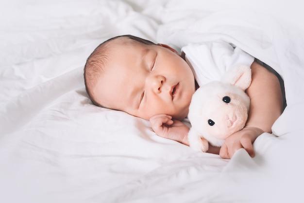 Ritratto di un neonato di una settimana che dorme pacificamente con un simpatico peluche nella culla