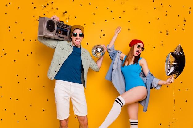 Ritratto di bella attraente allegro allegro eccitato coppia amici amicizia ballare divertirsi chill out riposo tempo libero divertimento isolato brillante vivido brillantezza vibrante colore giallo sfondo