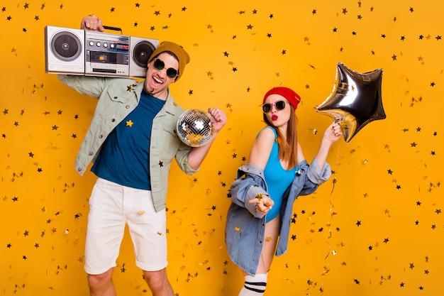 Ritratto di bello attraente fresco allegro divertente eccitato felice coppia amici amicizia ballare divertirsi tempo libero fine settimana riposo isolato brillante vivido brillantezza vibrante colore giallo sfondo