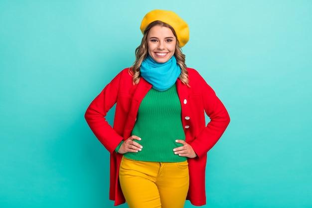 Ritratto di una bella ragazza bella e attraente che si gode la stagione invernale a piedi, mettendo le mani in vita, indossando abiti luminosi isolati su uno sfondo di colore verde acqua