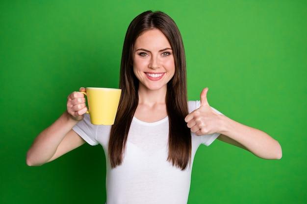 Il ritratto di una giovane donna bruna allegra e felice che beve cacao mostra il pollice in alto isolato su uno sfondo di colore verde