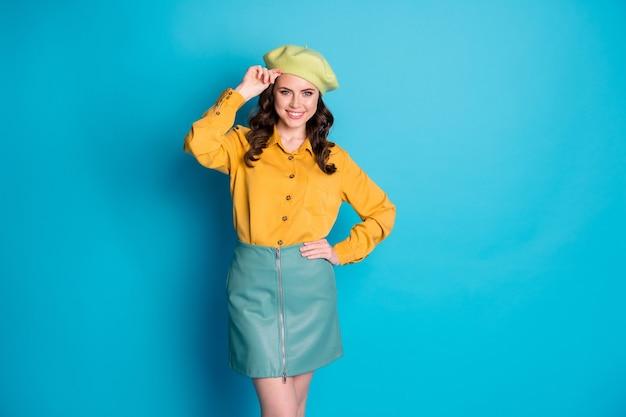 Ritratto di una bella ragazza dolce e adorabile che tocca il cappello francese si gode il riposo autunnale autunnale rilassato isolato su uno sfondo di colore blu