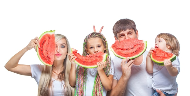 Ritratto oh famiglia felice con due bambini che tengono le fette di anguria davanti ai loro volti isolati su bianco