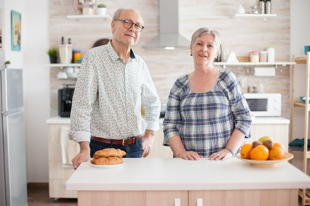 Ritratto di vecchia coppia allegra che esamina la macchina fotografica in cucina mentre prepara la colazione. felice uomo e donna in pensione.