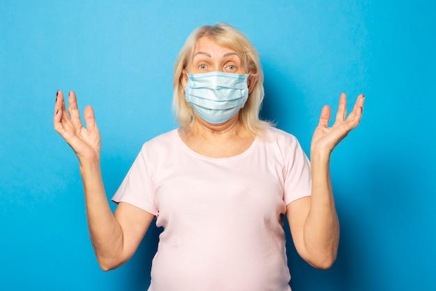 Ritratto di una donna anziana amichevole in una maglietta e una maschera protettiva medica scrollata di spalle le mani sulla parete blu. volto emotivo. concept virus, quarantena, aria sporca, pandemia. gesto di ansia, preoccupazione