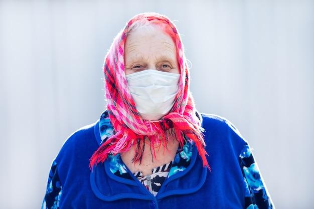 Ritratto di una vecchia nonna in una maschera protettiva. il problema della pandemia di coronavirus.
