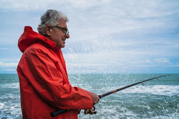 Ritratto di un uomo anziano che gode del tempo libero e pesca sugli scogli al mare. concetto di pesca.