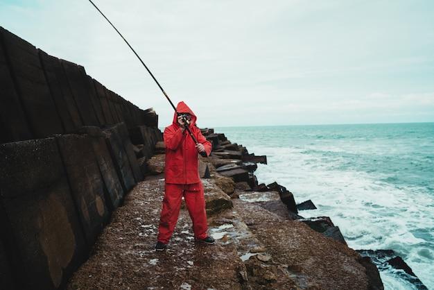 Ritratto di un uomo anziano che pesca sugli scogli al mare.