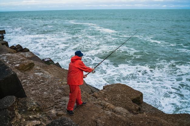 Ritratto di un uomo anziano che pesca in mare. concetto di pesca.