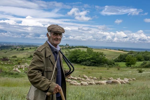 Ritratto di vecchio pastore che indossa un berretto piatto e una giacca verde che sorride sul prato