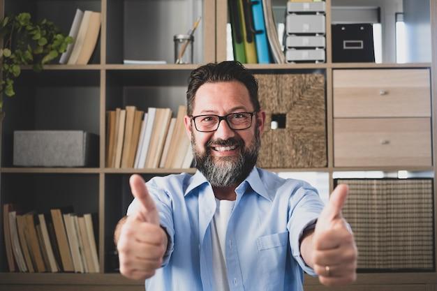 Ritratto di un uomo felice e allegro sorridente e guardando la telecamera con la mano del dito in alto. uomo d'affari di sesso maschile che si diverte dopo aver ricevuto buone notizie di lavoro