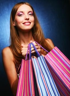 Ritratto di una giovane ragazza adulta felice con i sacchetti colorati