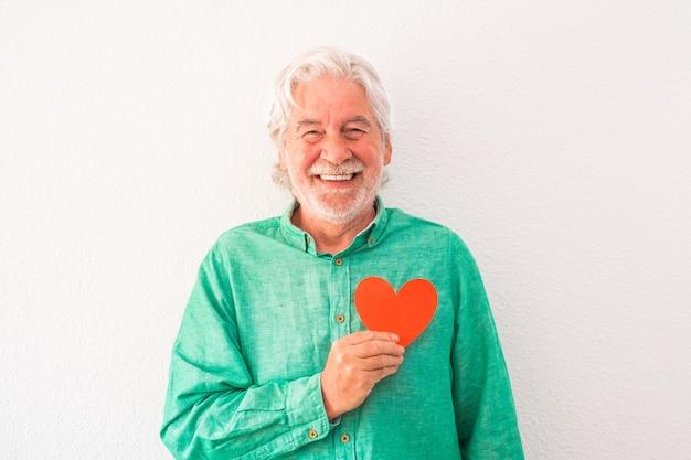 Ritratto di un uomo maturo che sorride e guarda la telecamera con un cuore rosso sul petto - uomo con problemi cardiaci e concetto di malattia