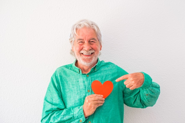 Ritratto di un uomo maturo che sorride e guarda la telecamera con un cuore rosso sul petto