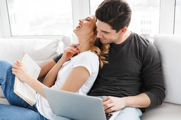 Ritratto di coppia ottimista che utilizza laptop e legge un libro mentre è seduto sul divano in una stanza luminosa a casa