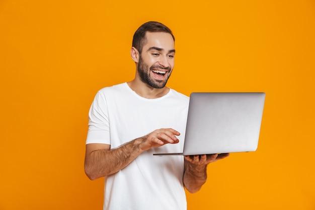 Ritratto di uomo ottimista anni '30 in maglietta bianca che tiene computer portatile d'argento, isolato