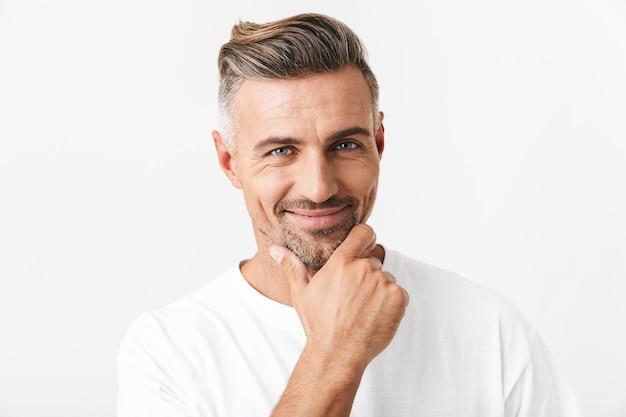 Ritratto di un uomo ottimista di 30 anni con setola che indossa una maglietta casual che sorride e tocca il mento isolato su bianco