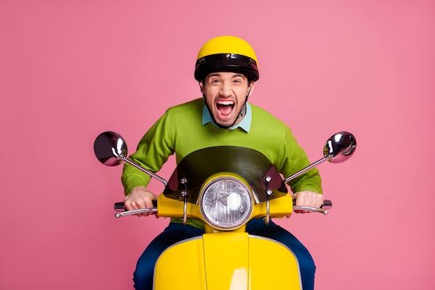 Ritratto di ragazzo felicissimo in sella a una moto urlo bocca aperta