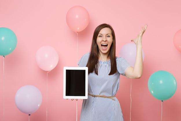 Ritratto di donna felice felicissima in abito blu che tiene un computer tablet pc con schermo vuoto vuoto che allarga le mani su sfondo rosa pastello con mongolfiere colorate. concetto di festa di compleanno.