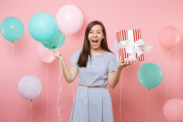 Ritratto di felicissima donna felice che indossa abito blu con scatola rossa con regalo regalo e mongolfiere colorate su sfondo rosa brillante. festa di compleanno, concetto di emozioni sincere della gente.