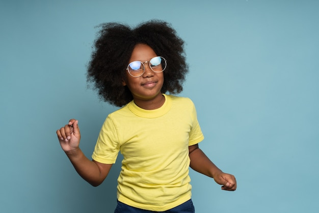 Ritratto di una bambina felicissima con i capelli ricci con gli occhiali che balla e si sente benissimo. colpo dello studio isolato su priorità bassa blu. concetto di infanzia