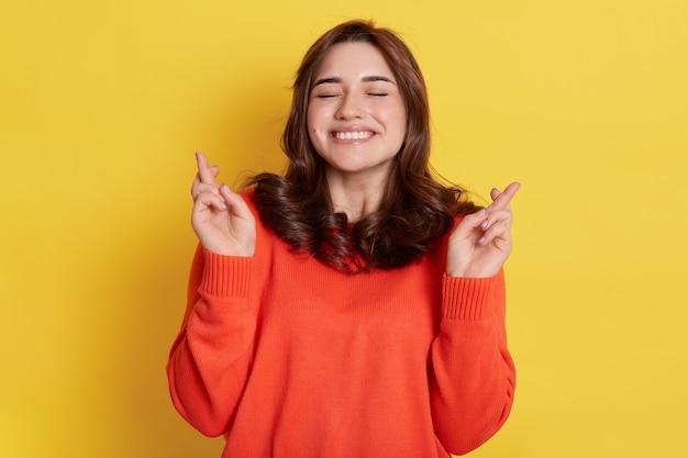 Ritratto di giovane donna caucasica felicissima con i capelli scuri che solleva i pugni con le dita incrociate dalla gioia o dalla felicità, tiene gli occhi chiusi e stringendo i denti, spera di successo.