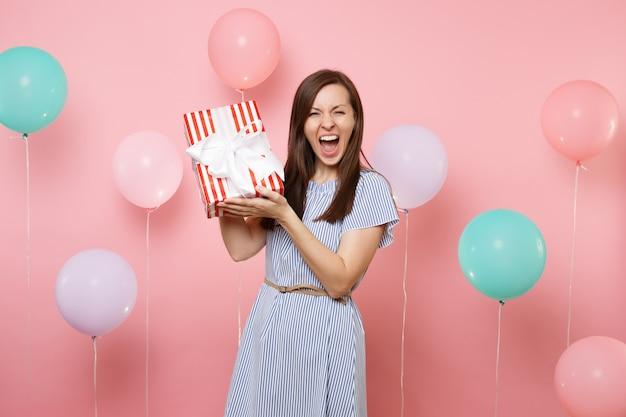 Ritratto di felice giovane donna in abito blu urlando tenendo scatola rossa con regalo presente su sfondo rosa pastello con mongolfiera colorata. festa di compleanno, concetto di emozione sincera della gente.