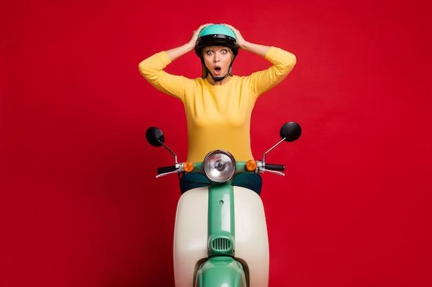 Ritratto della ragazza sopraffatta che si siede sul fronte scioccato del ciclomotore