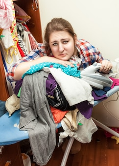 Ritratto di casalinga oberata di lavoro che fa il stiro