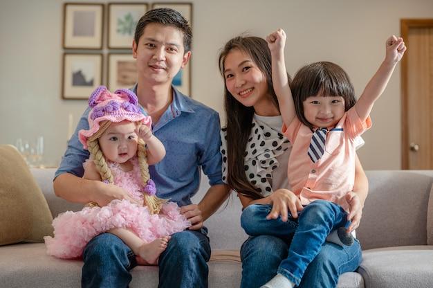 Ritratto di genitori felici la famiglia piena si diverte seduti sul divano nelle attività di svago del soggiorno