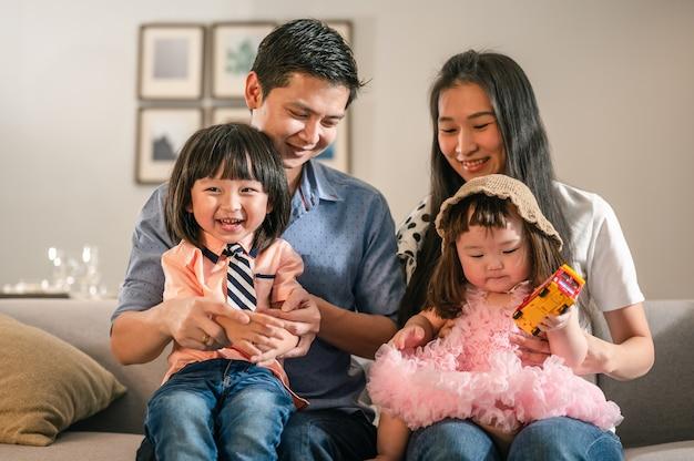 Ritratto di genitori felici la famiglia piena con i bambini si divertono seduti sul divano nel tempo libero del soggiorno