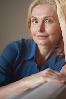 Ritratto di una donna matura pacifica che guarda la telecamera con un sorriso amichevole mentre si rilassa sul divano a
