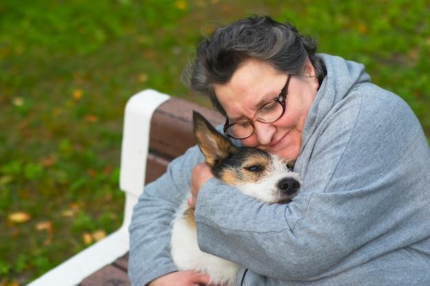 Ritratto di una donna pensionato che abbraccia il suo cane
