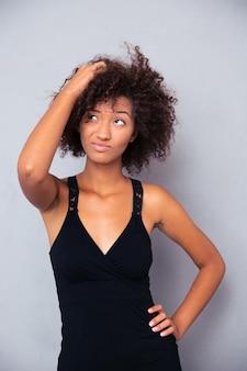 Ritratto di pensieroso afro american donna alzando lo sguardo oltre il muro grigio