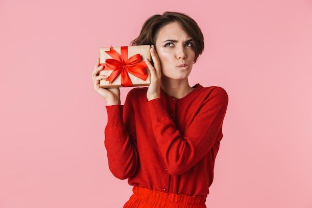 Ritratto di una bella giovane donna pensierosa che porta vestito rosso in piedi isolato