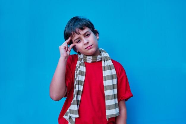 Un ritratto di ragazzo pensieroso in maglietta rossa e sciarpa