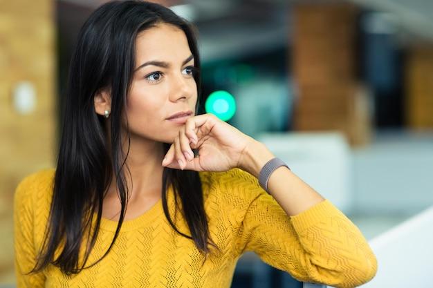 Ritratto di una donna d'affari pensierosa in piedi in ufficio